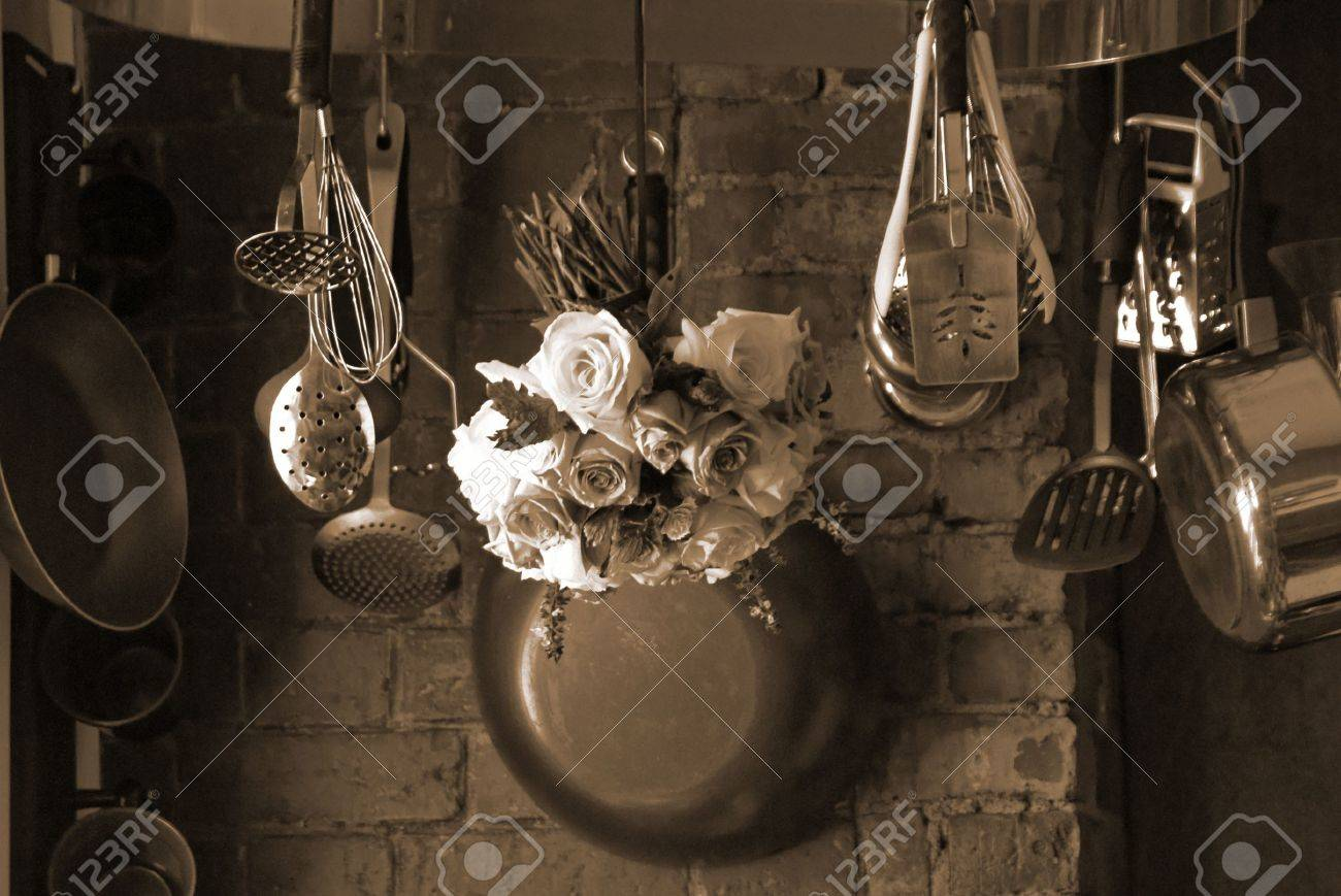 Sepia Toned Image Of Country Kitchen With Roses Hanging From Stock