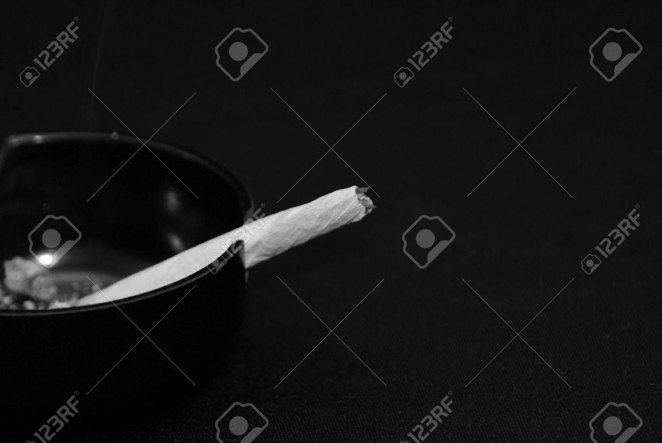 Striking black and white image of hand rolled cigarette in black