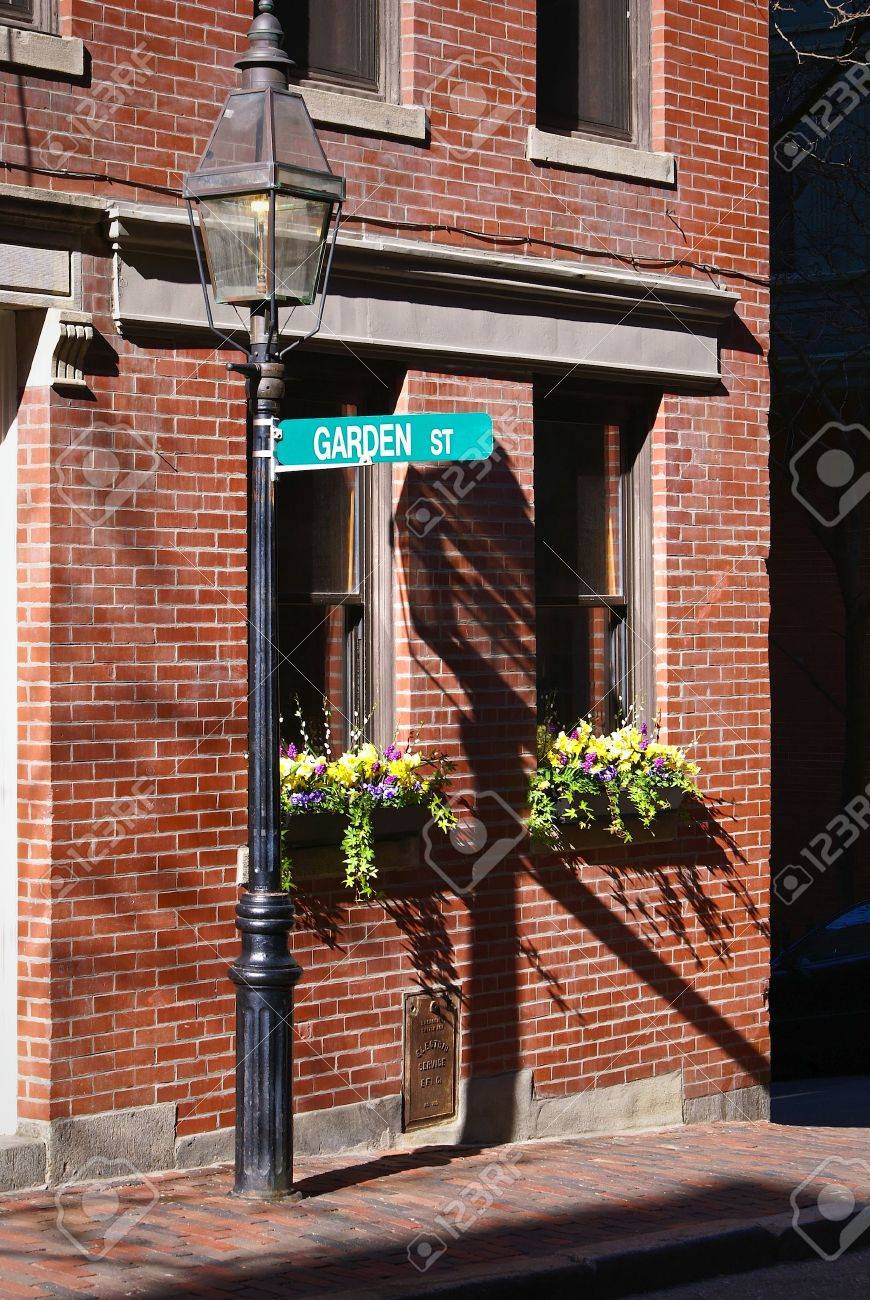 Garden Street Sign In Bright Sun Light Hangs From Gas Lamp Post Above Two  Flower Boxes