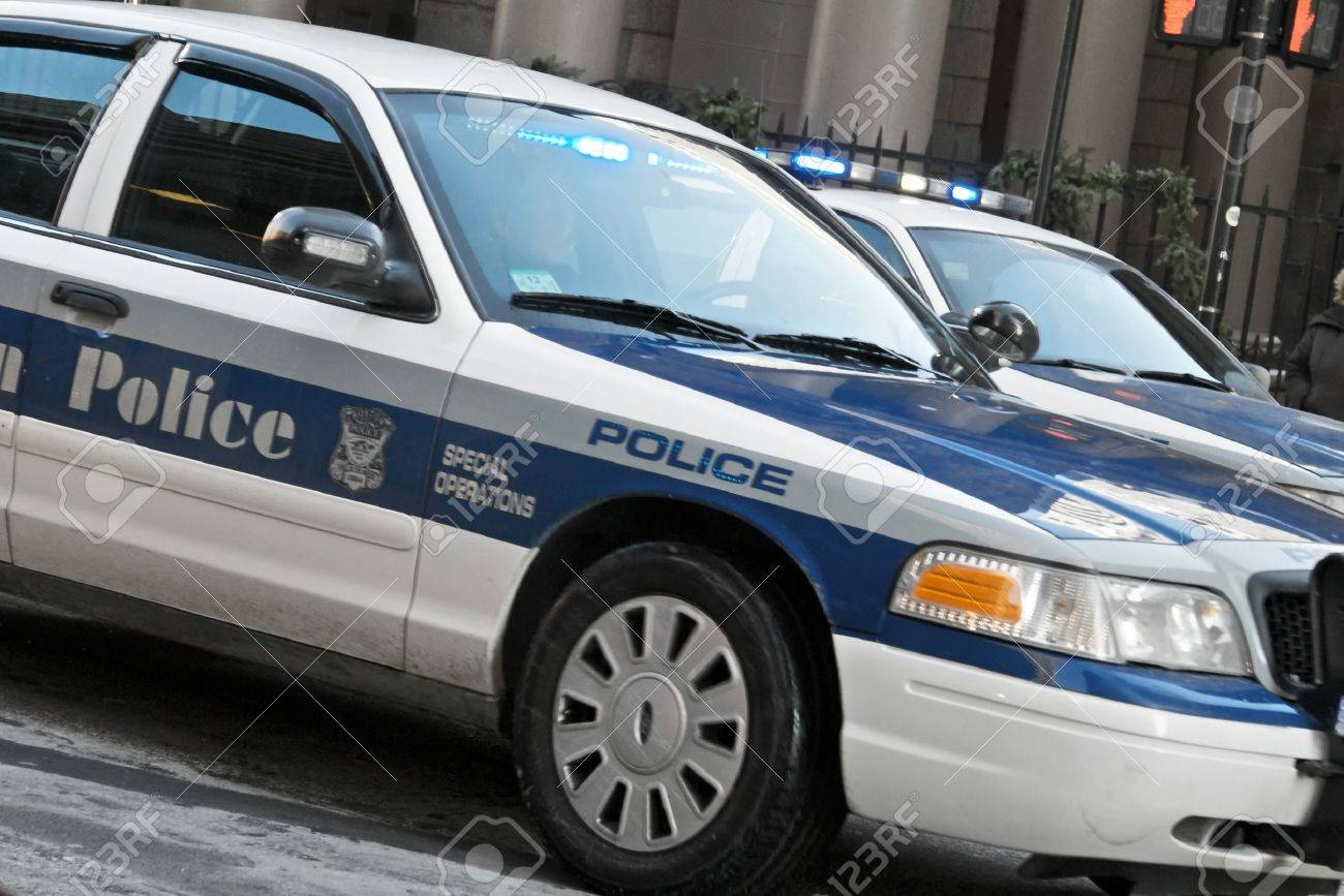 two boston police cars with lights flashing in motion stock photo