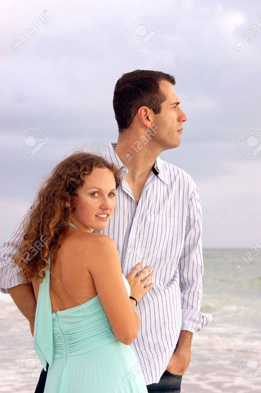 An attractive well dressed young couple  with their bodies facing each other, the man is looking out to the ocean in profile. The wooman is turned and looking at viewer Stock Photo - 4919811