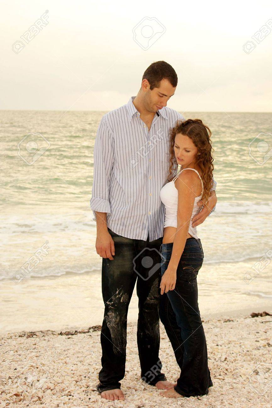 A tall handsome yooung man is holding a beautiful sexy woman close and looking down at her smiling as she looks at the ground Stock Photo - 4940328