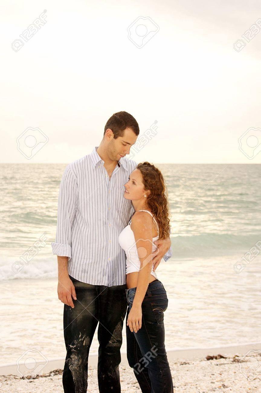 ed3f9ad4a14f94 Standard-Bild - Tall Mann sucht nach einer kürzeren Frau und ihr Betrieb in  der Nähe des Strandes mit Ozean-Wellen im Hintergrund.