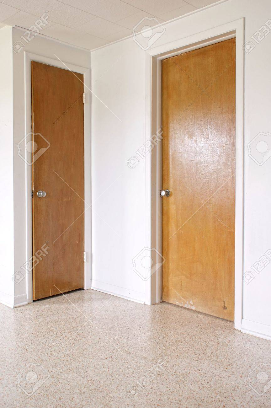 Two Closed Wooden Doors On White Walls With A Terrazzo Floor