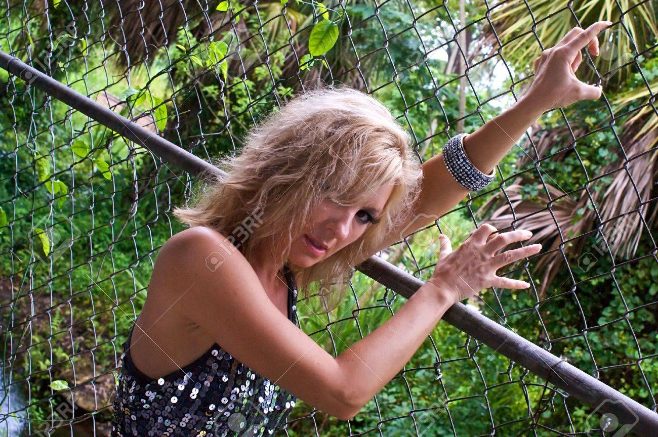 A beautiful blonde woman is holding  a chain link fence and looking like she is climbing it, looking back over her shoulder at the viewer, wearing a silver sequined dress with trees in the background. Stock Photo - 5811623