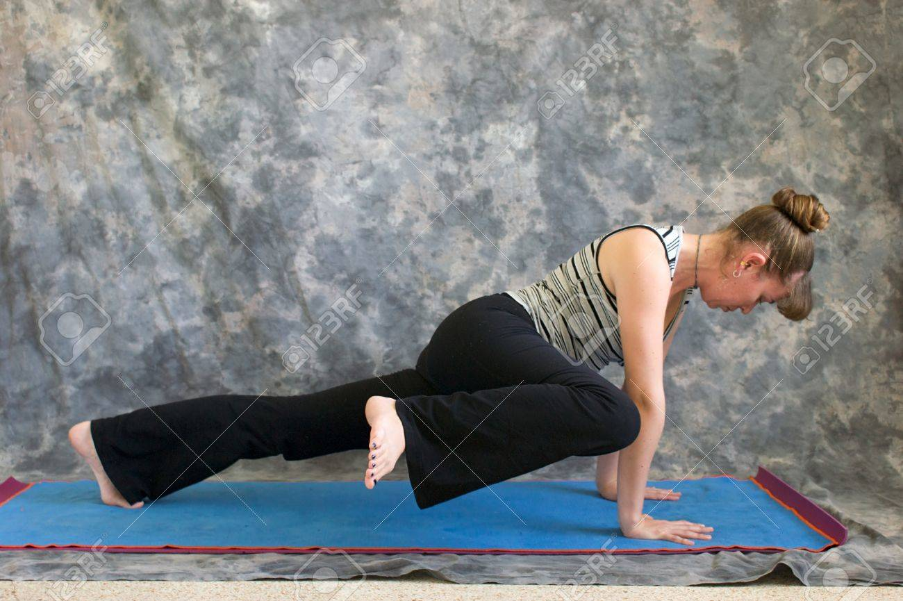 Jeune Femme Sur Le Tapis De Yoga Yoga Posture Haute Planche Genou A Coude Variation Sur Un Fond Gris De Profil Tourne Vers La Droite Eclairee Par La Lumiere Du Soleil Diffuse
