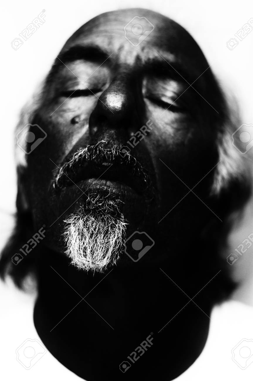 Dark high contrast black and white portrait of man looking dead focus on nose and