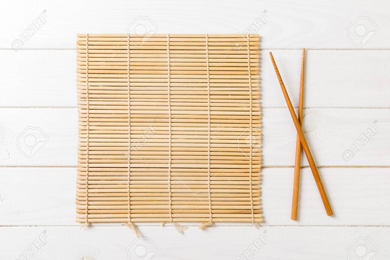 Two Sushi Chopsticks With Empty Bamboo Mat Or Wood Plate On Wooden