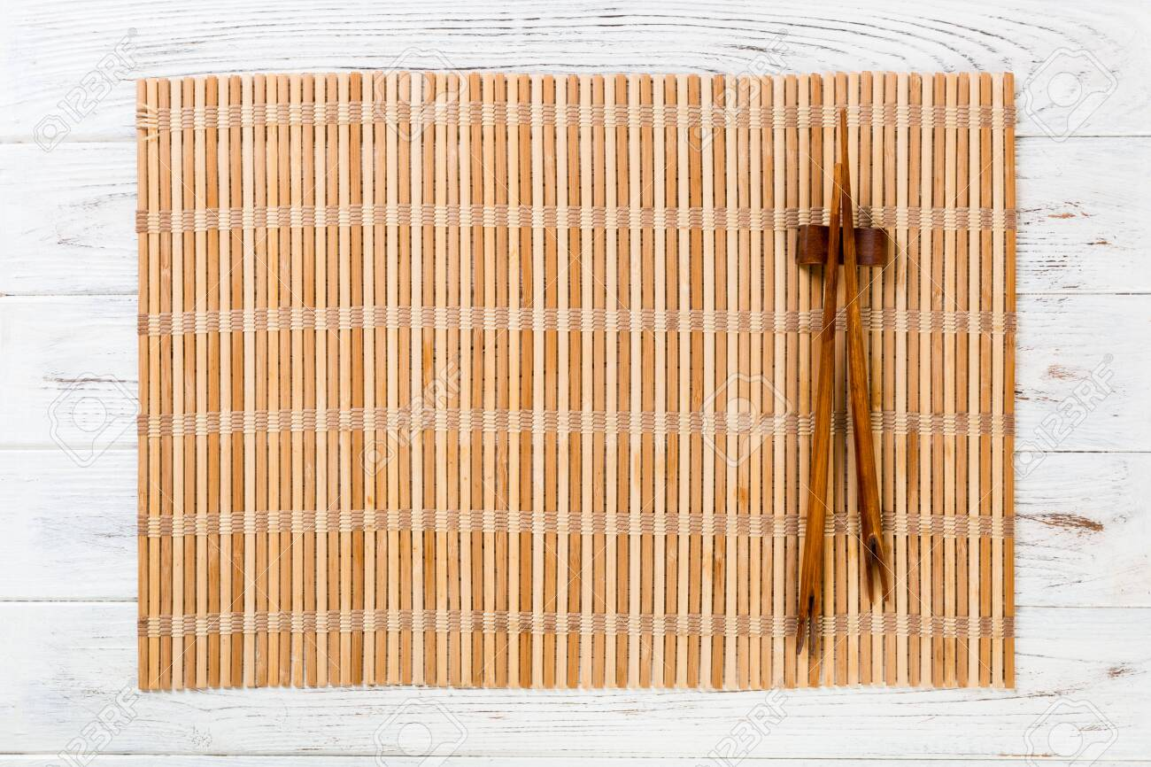 Two Sushi Chopsticks With Empty Brown Bamboo Mat Or Wood Plate