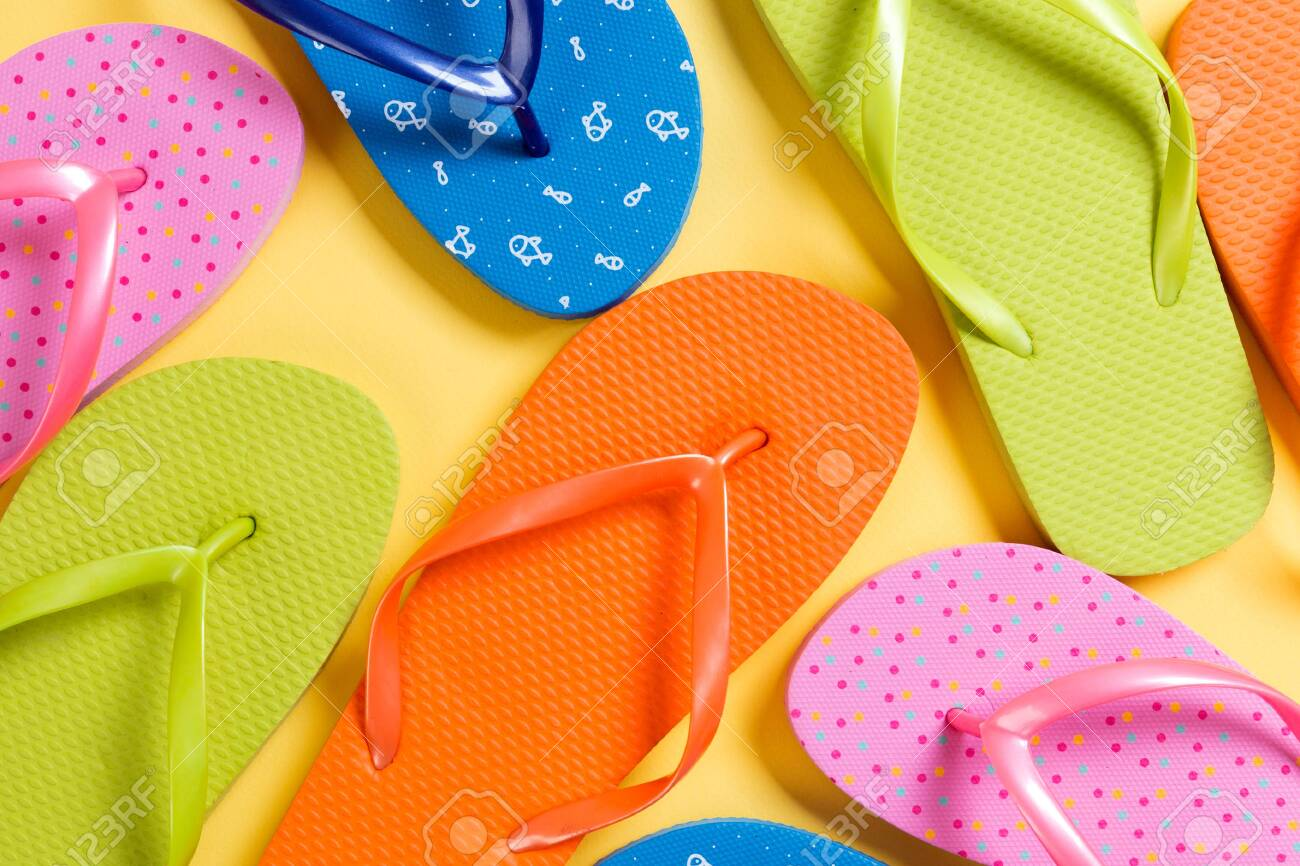 many colored flip flops on yellow background. Copy space top view. - 141283297