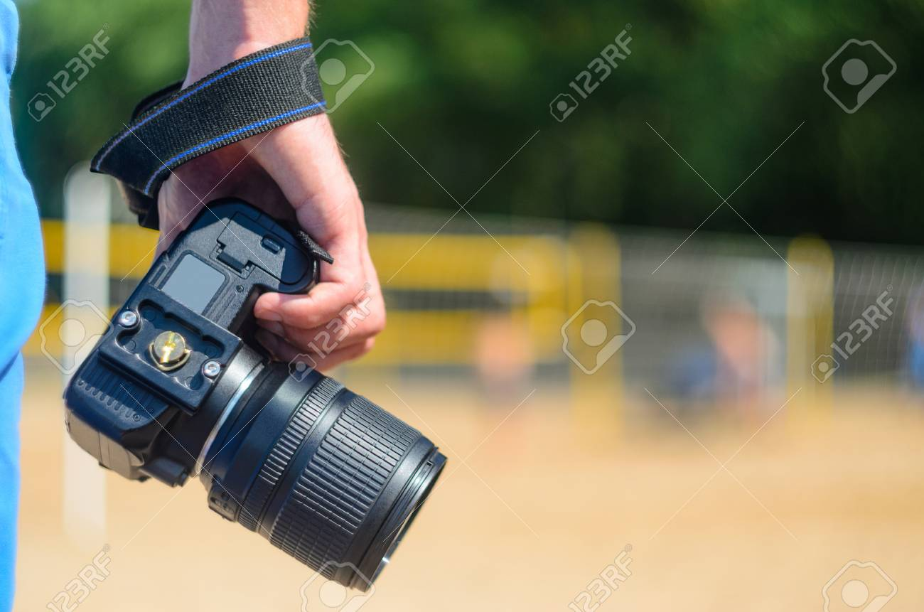 Dslr Camera In The Hands Of A Photographer On A Sandy Beach Close Stock Photo Picture And Royalty Free Image Image 84481254