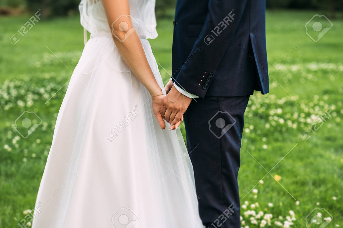 Hands of bride and groom. New young couple holding hands after their wedding. Young married couple holding hands, ceremony wedding day. Closeup view of married couple holding hands - 125107828
