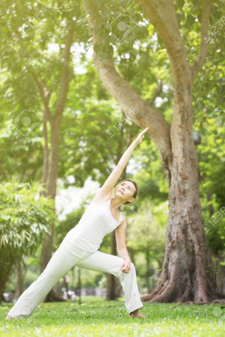 Asian Woman In White Shirt And White Trousers In Meditation And Yoga Pose  In Garden Stock