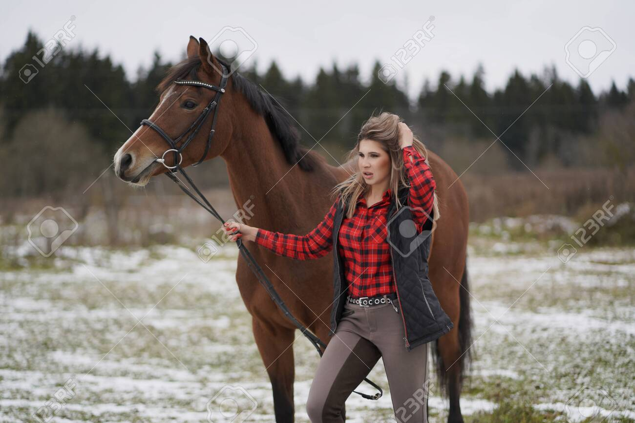 A beautiful girl in a fashionable shirt walks with her horse in early winter. - 134005964