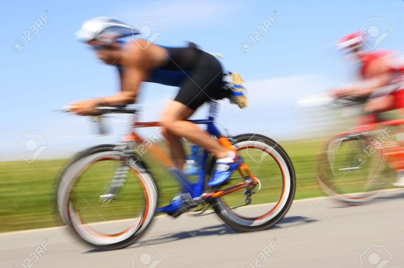 Two bicyclist race through the countryside. Their speed is excentuated by the motion blur Stock Photo - 2735255