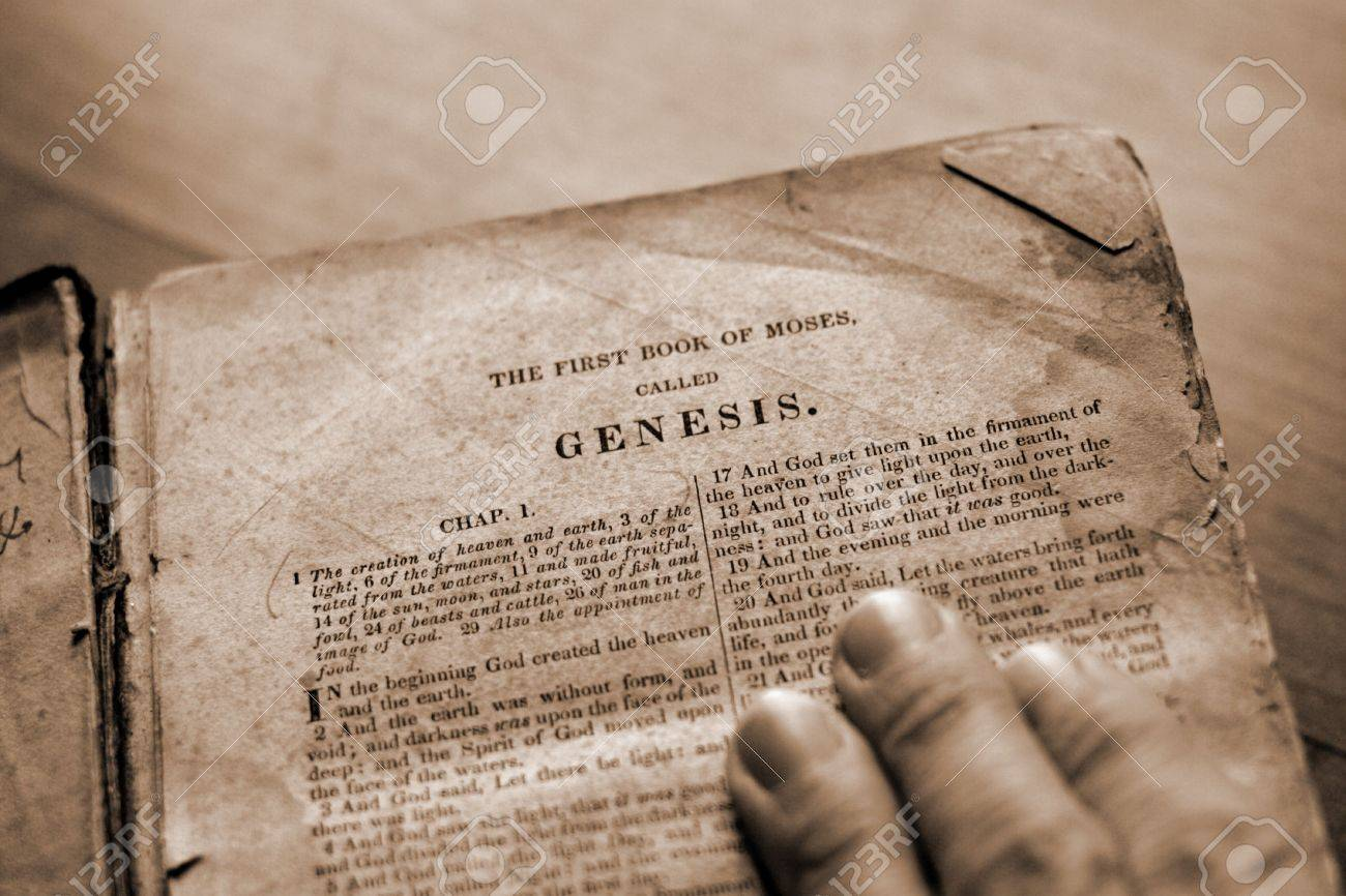a hand on the bible with page turned to genesis stock photo