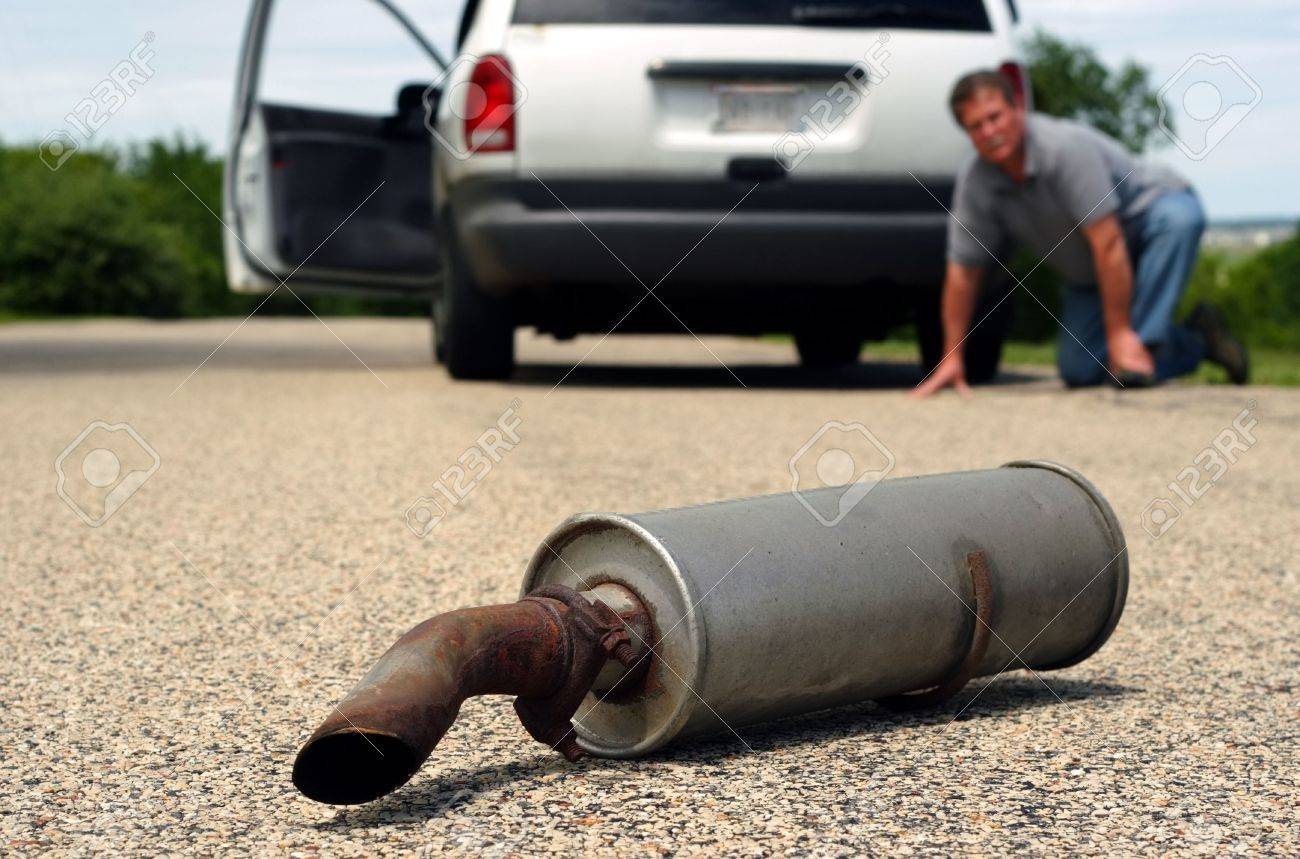 A man kneals on the ground by his car and looks back to see his car's muffler laying on the ground Stock Photo - 2853115