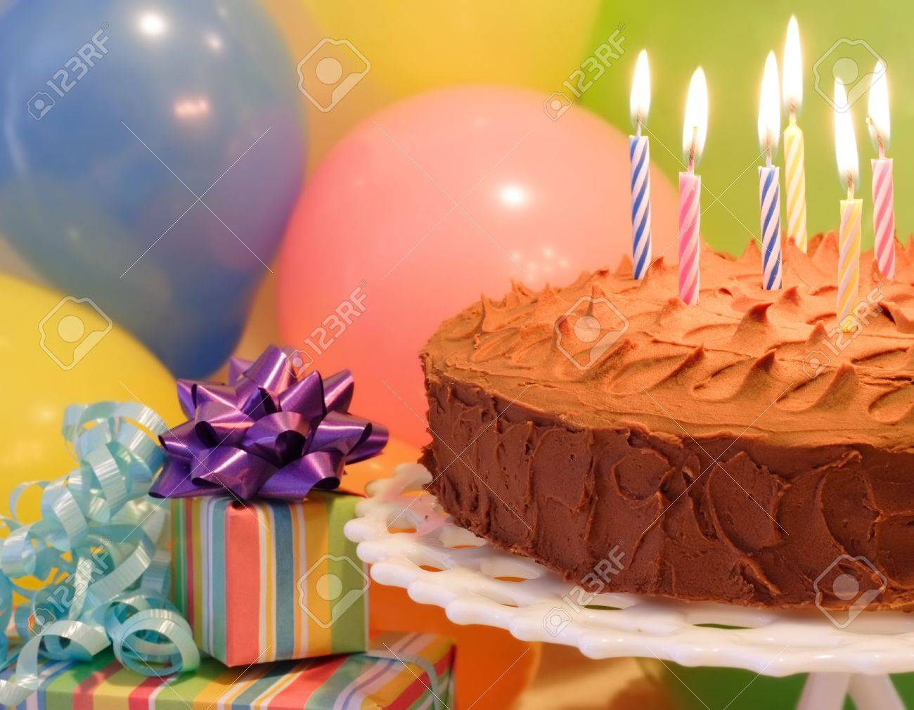 A Birthday Cake With Lit Candles Balloons And Presents Stock Photo