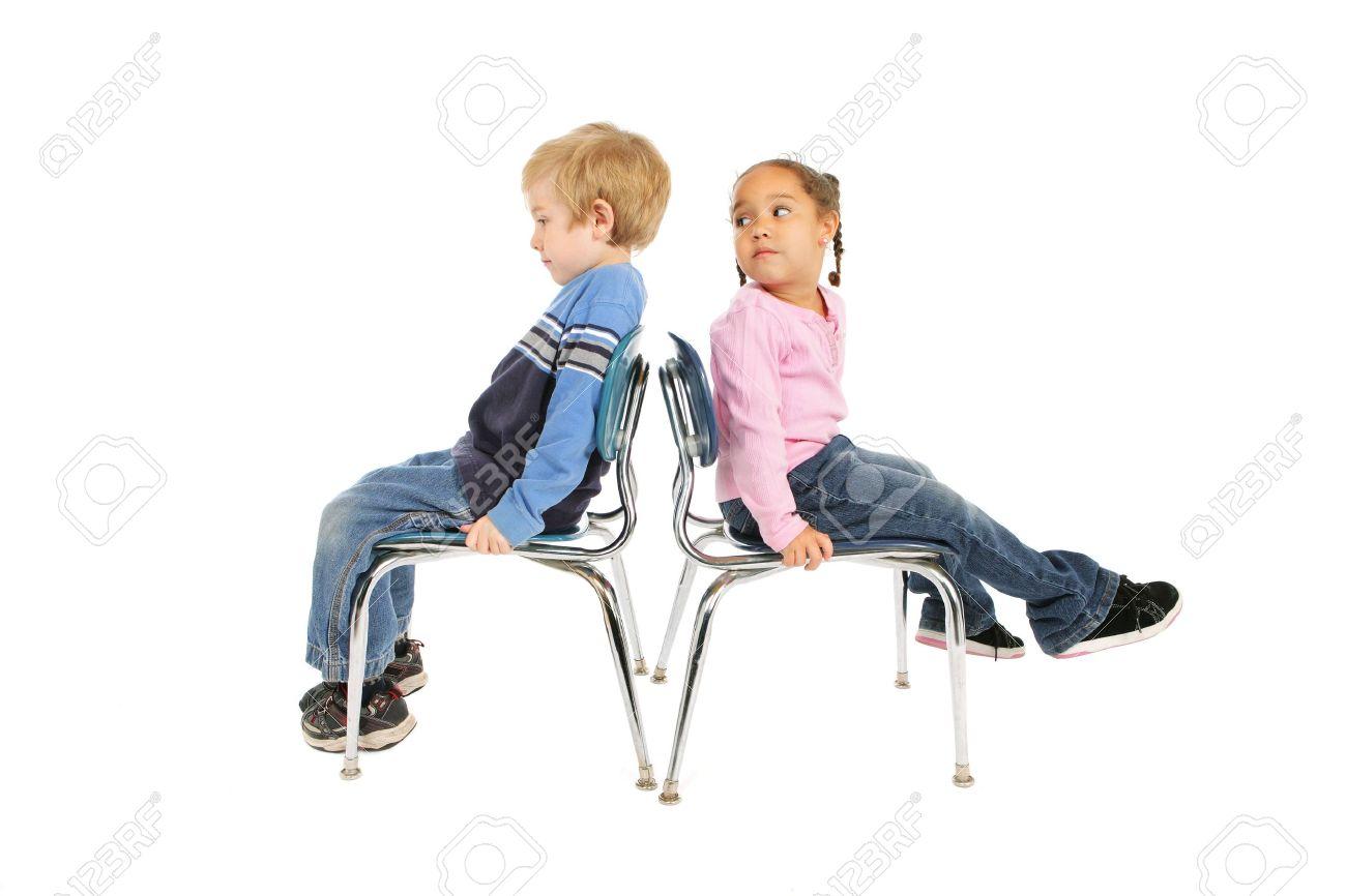 Dos niños sentados en sillas que están de espaldas