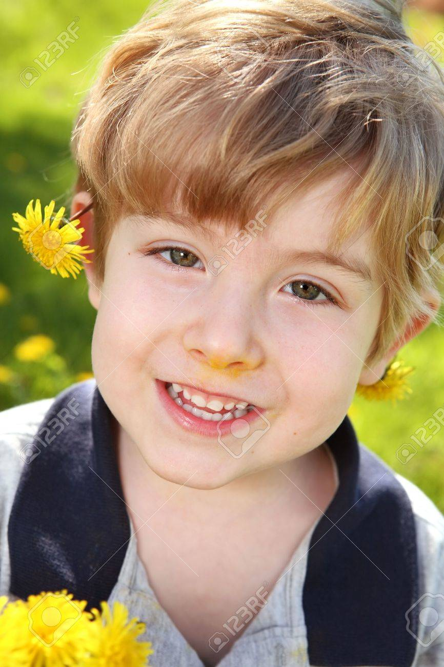 A close up of a young boy standing in a field of dandelions Stock Photo - 5201794