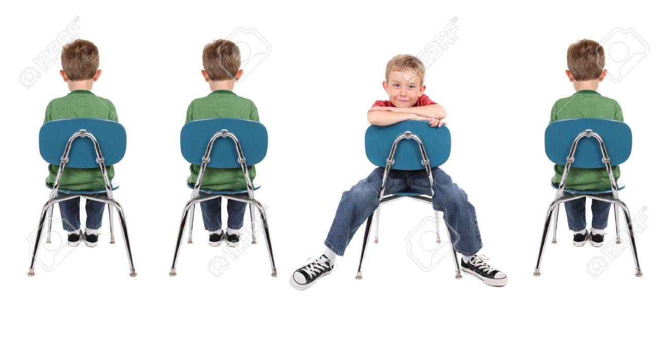 A group of boys sit in school chairs. One is facing backwards and is wearing  sc 1 st  123RF.com & A Group Of Boys Sit In School Chairs. One Is Facing Backwards ...