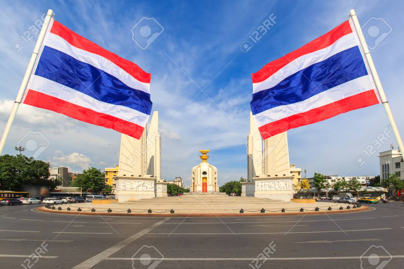 Democracy monument with blue sky and thai flag foreground in sunshine day, Bangkok, Thailand - 67084166