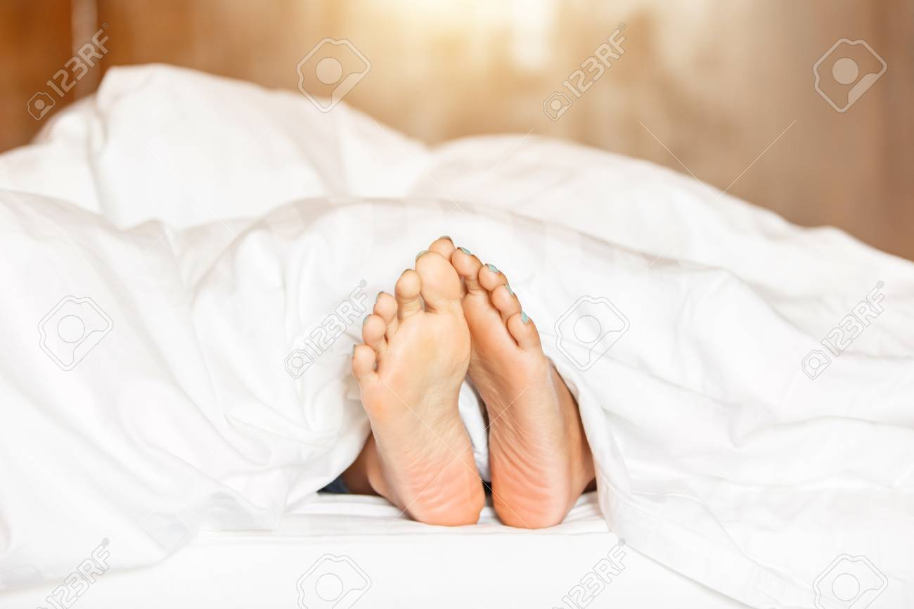 623df1a0f1 Stock Photo - Woman feet under white blanket side view. Beautiful young woman  feet with blue pedicure on the bed. Sleeping woman legs under the white ...