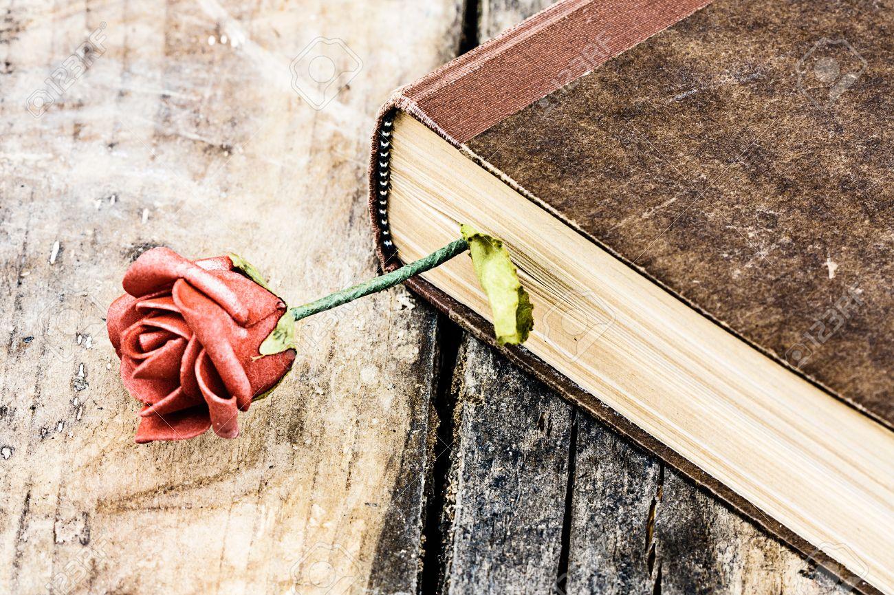 Livre fermé sur le bureau en bois de rose banque dimages et photos