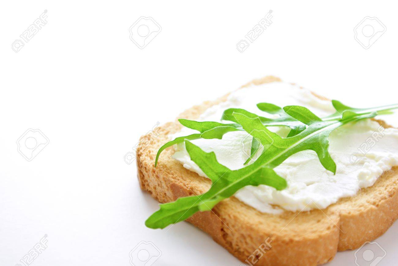 A crusty toasted bread whith cheese and rocket salad leaves isolated on a white background Stock Photo - 10017781