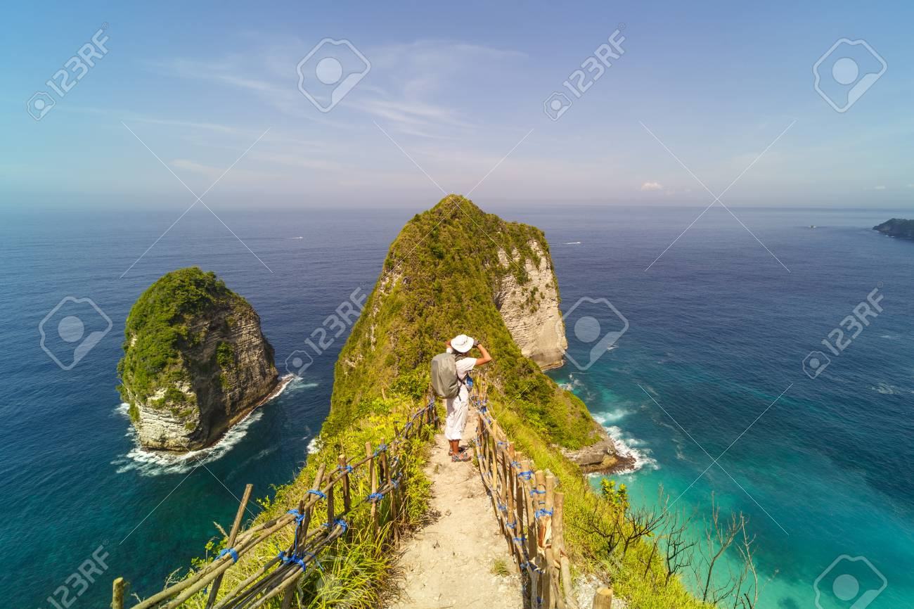 Mens backpack standing on Kelingking beach cliff on Nusa Penida