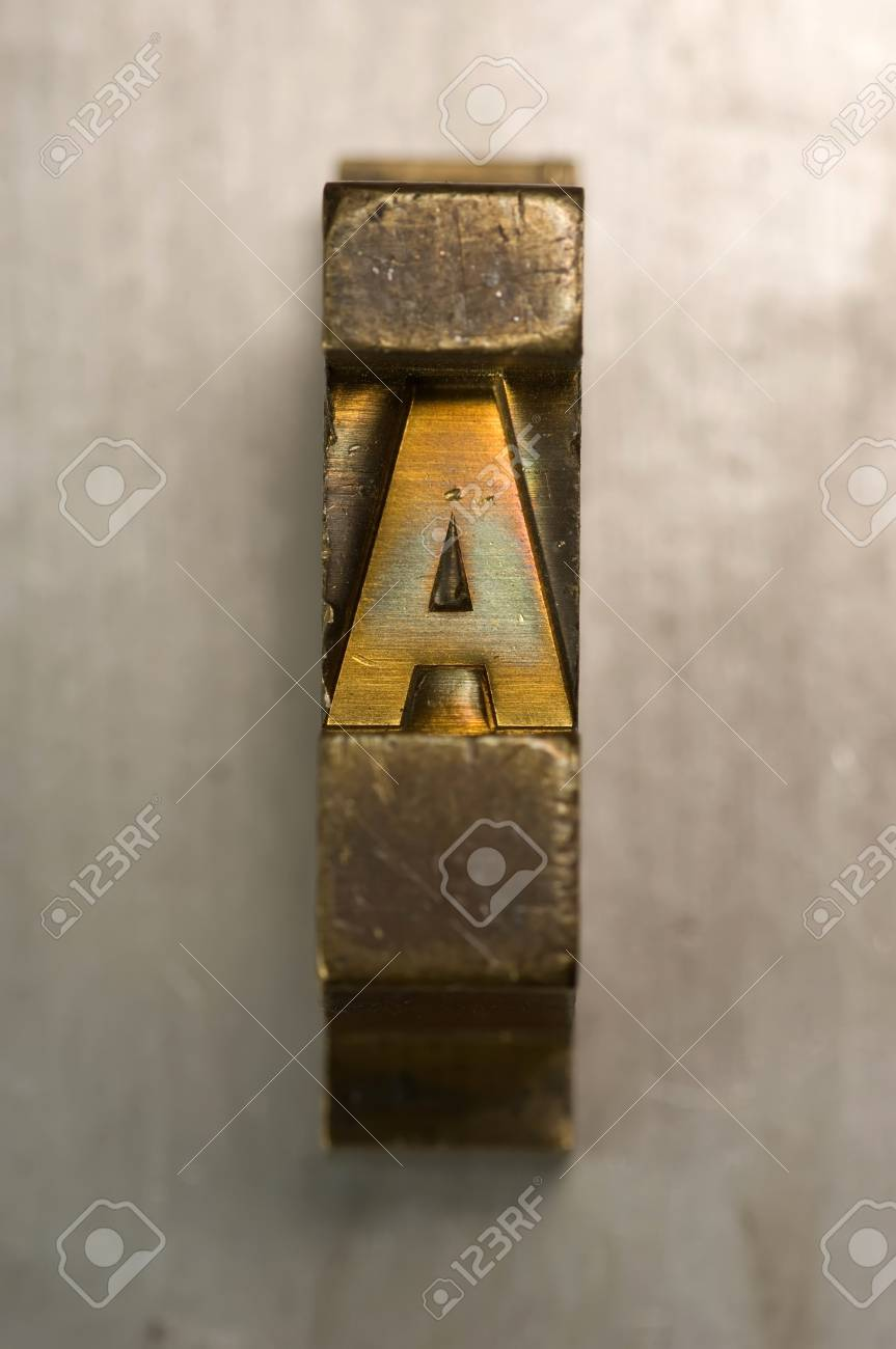 Brass / Gold colored letterpress piece on silver metal background Stock Photo - 4065795