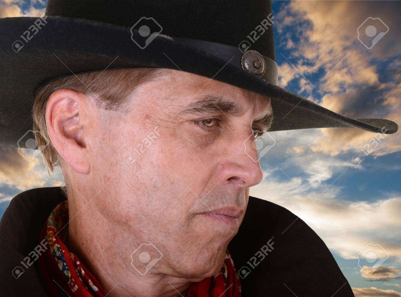 Profile Of Handsome Serious Man Wearing A Black Cowboy Hat And Red Bandana Against Beautiful Sunset