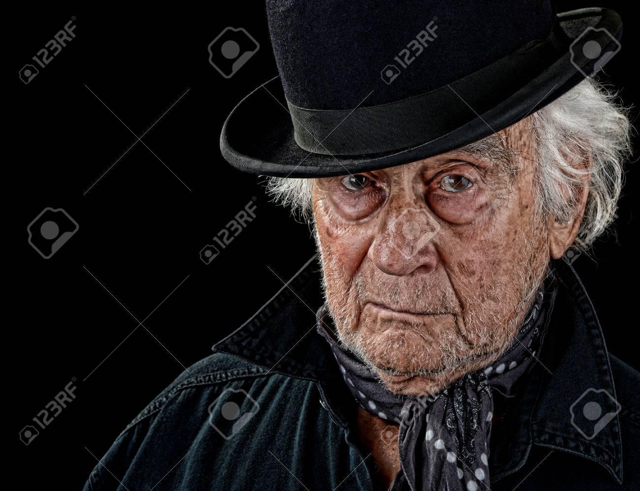 0b912537dda0f Banque d'images - Cru regardant vieil homme avec un manteau noir, écharpe  grise et chapeau melon noir regardant droit dans la caméra isolée sur fond  noir