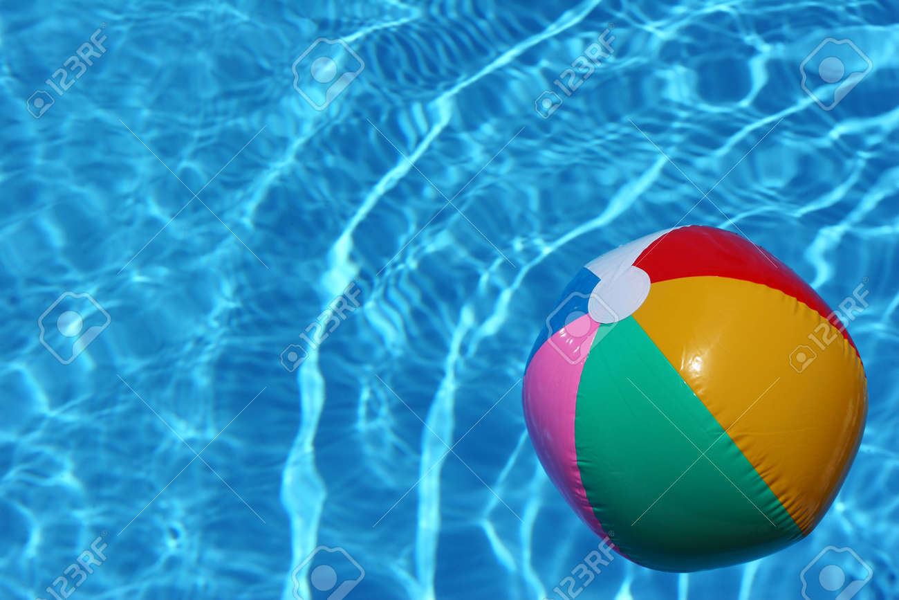 Swimming Pool Beach Ball Background bright beach ball in blue pool stock photo, picture and royalty