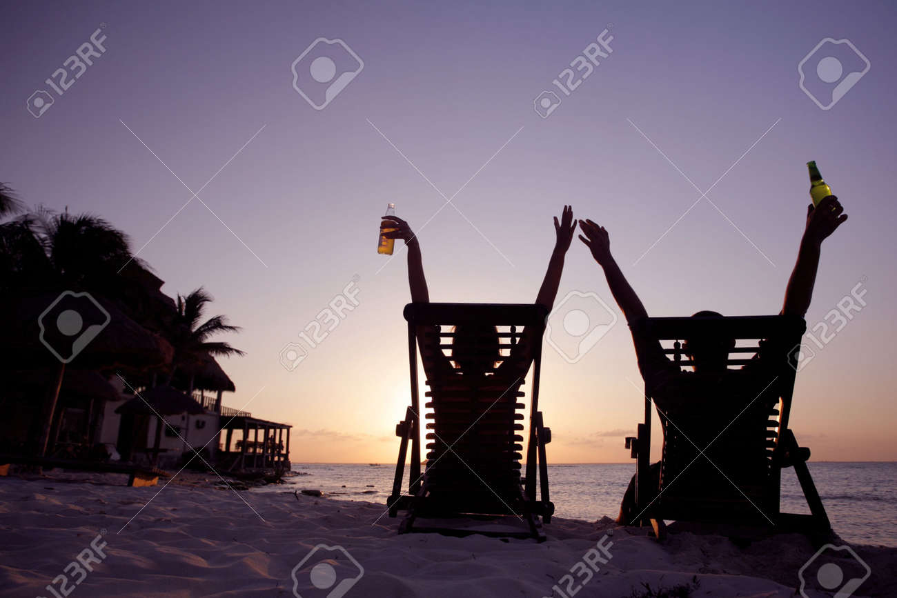 Couple stretching in deckchairs at sunset Stock Photo - 2954022