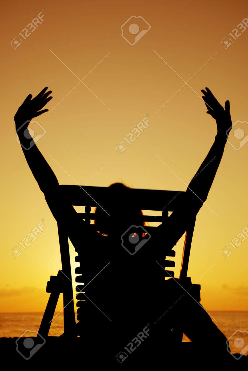 Woman drinking beer in a deckchair at sunset Stock Photo - 2954014