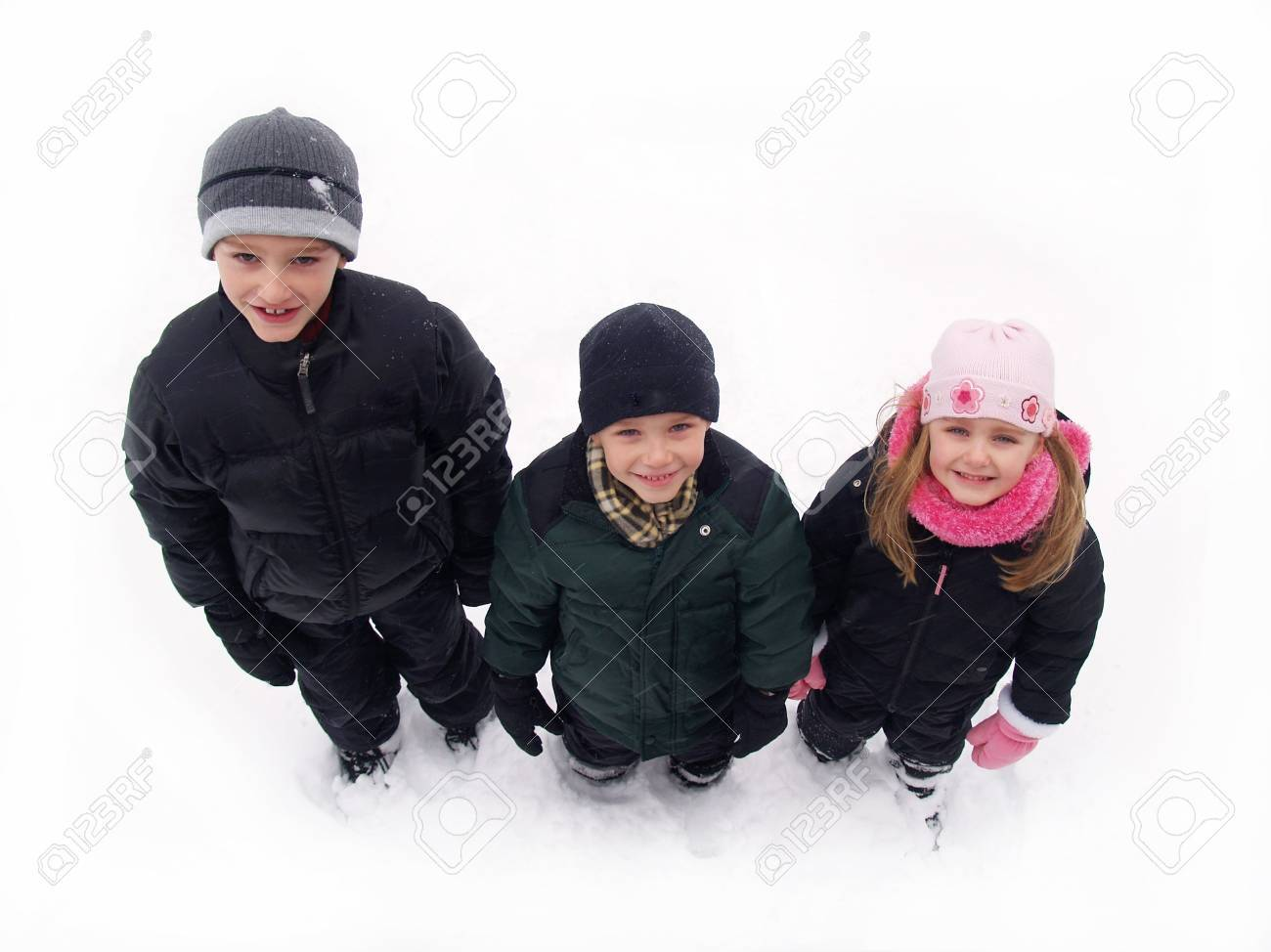three children in winter clothes standing in the snow Stock Photo - 2340251