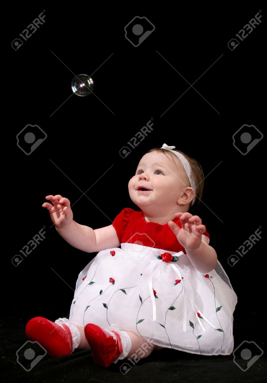 Cute Baby Girl In A Red And White Dress Looking Up At A Single ...