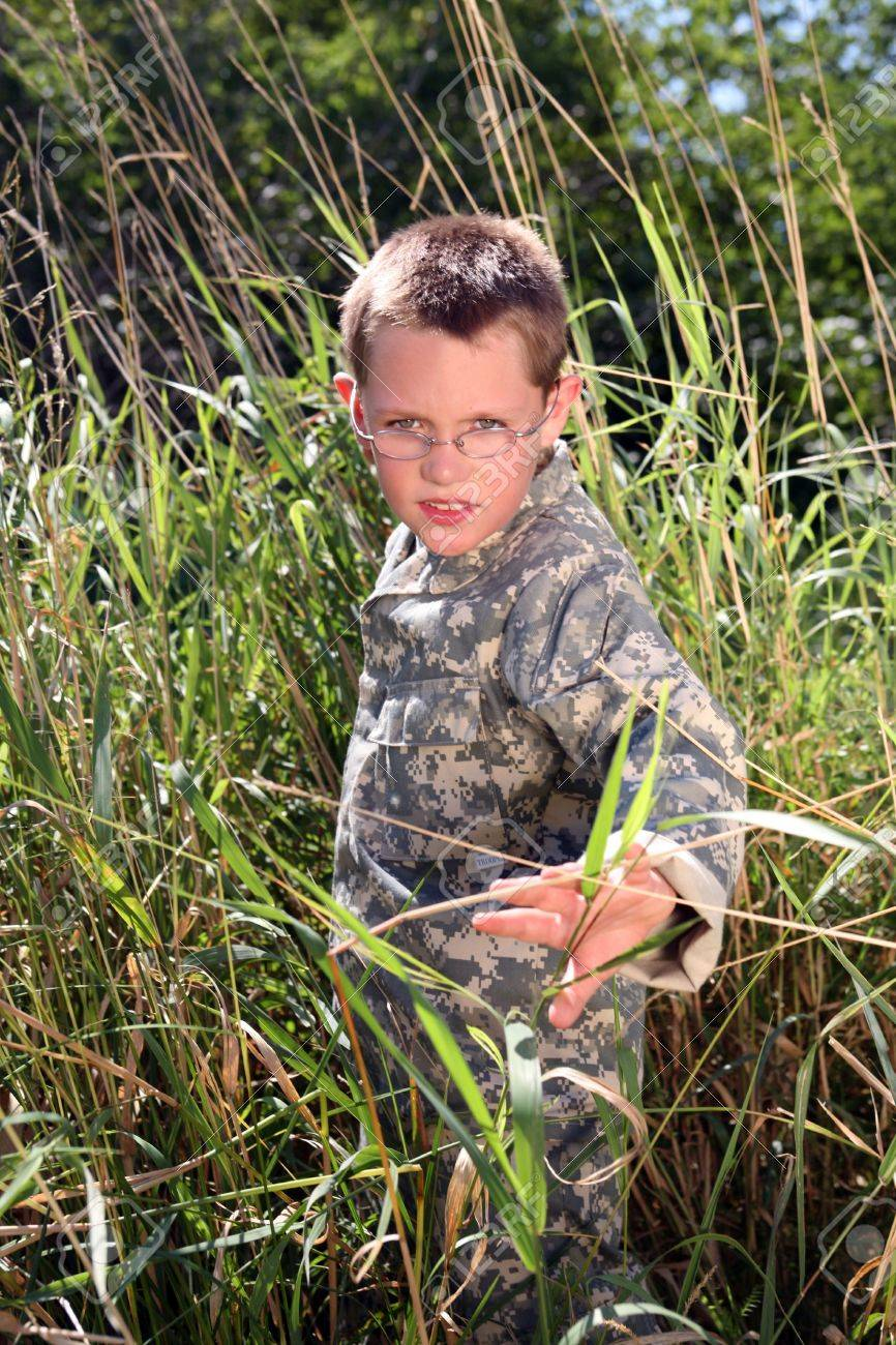 young boy in camoflauge hiding in the tall grass Stock Photo - 4253953