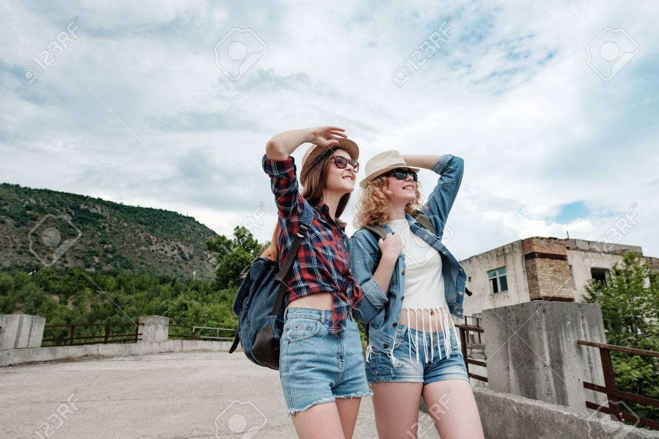 Stock Photo - Two girls in hats and glasses are traveling through a  mountain valley through a concrete abandoned bridge 8762b975d6790