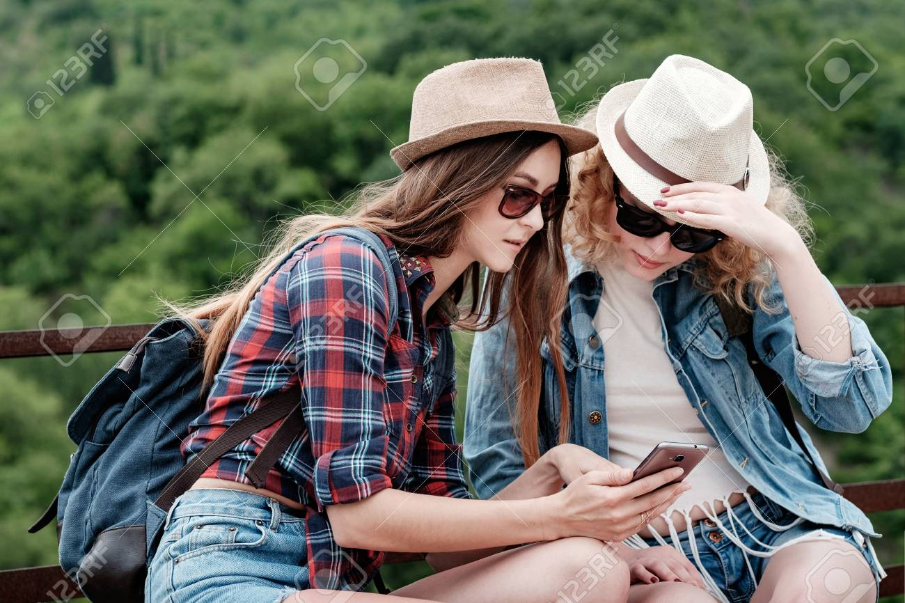 Stock Photo - Two girls travelling in hats and sunglasses using smartphone  navigating system at nature 040cd48cfac17