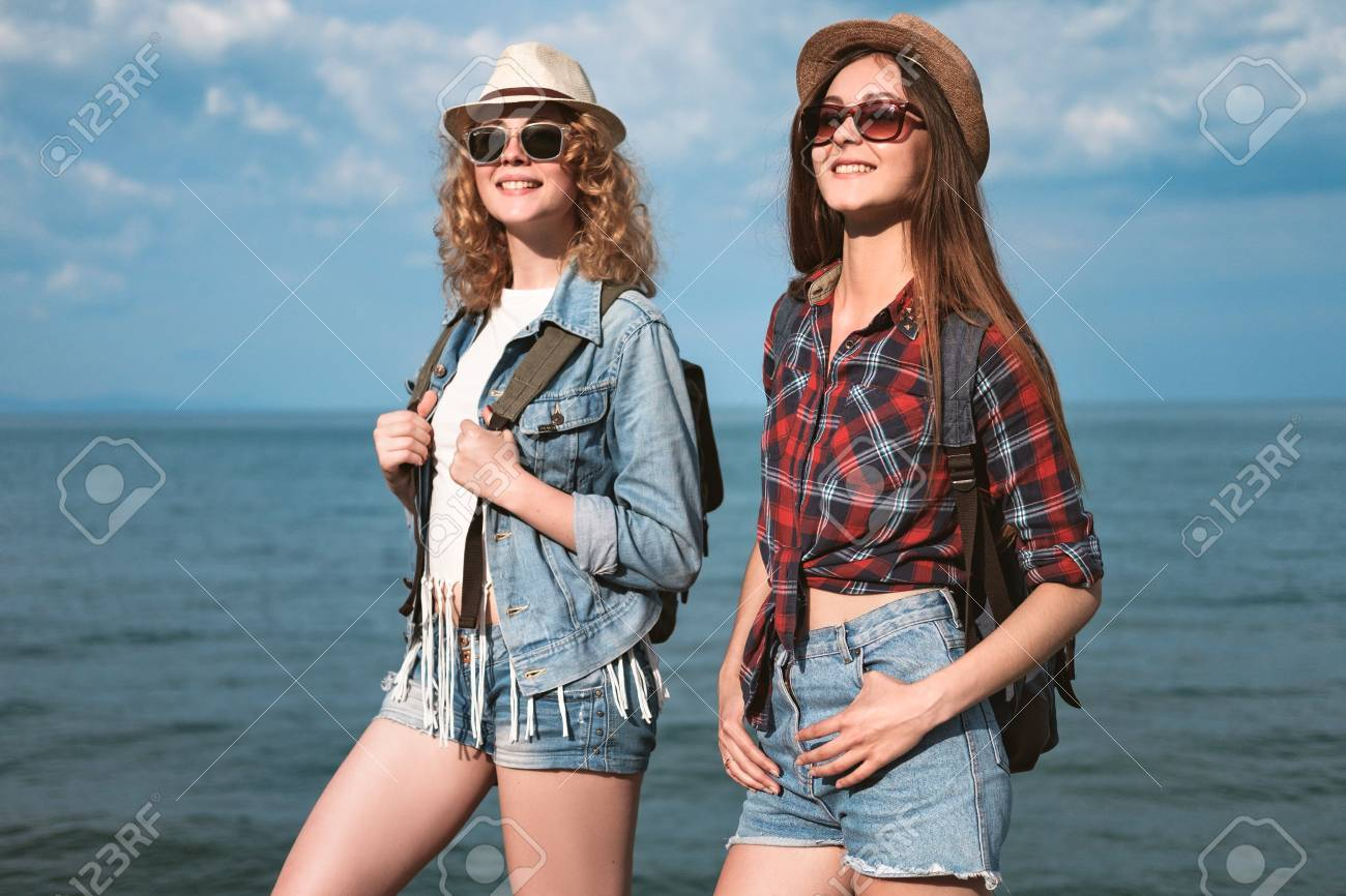 7cf82583e53 Two young girls in shorts and hats are traveling along the seaside..
