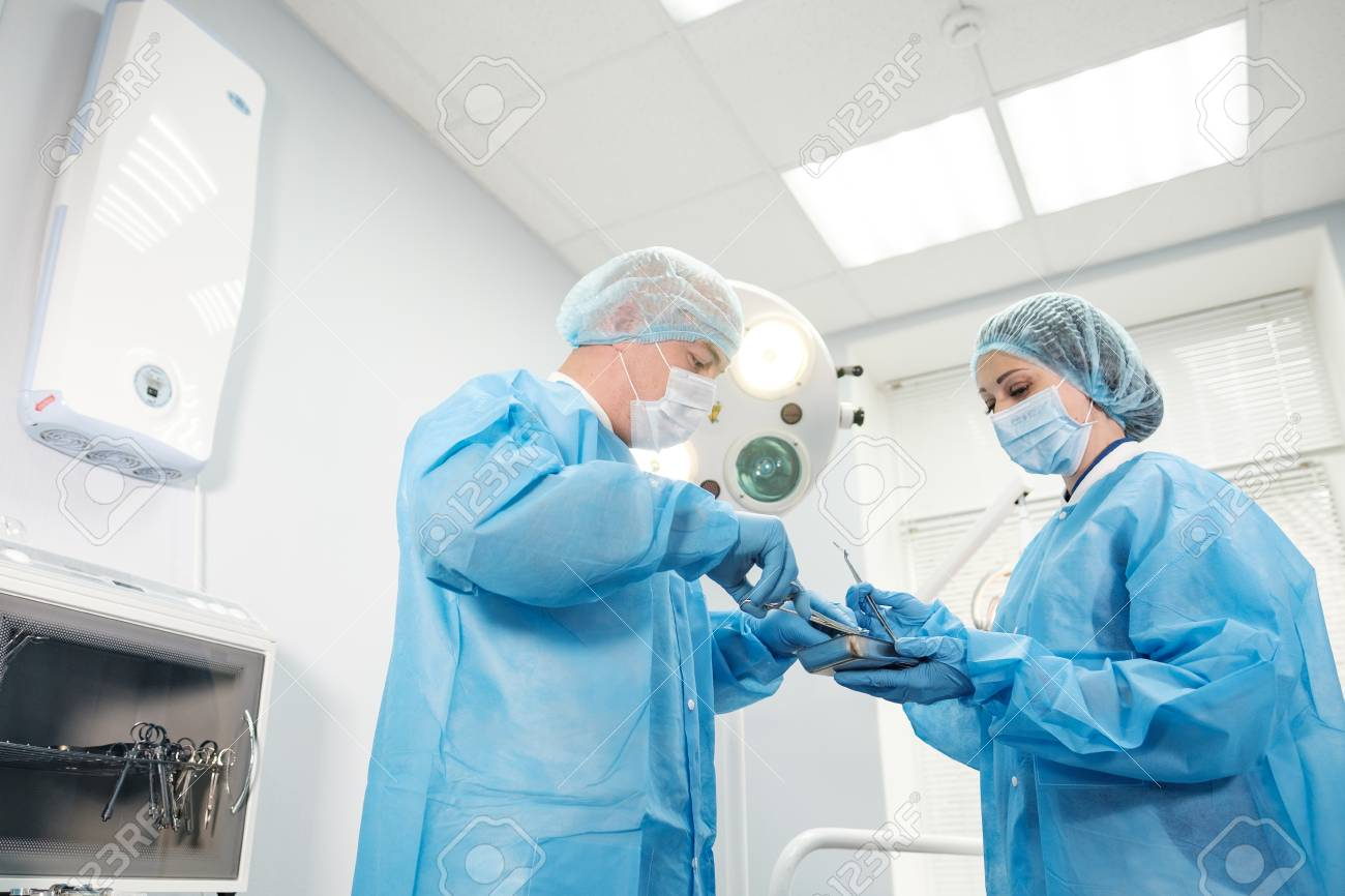 Male Doctor Anesthetist And Nurse In A Dressing Gown In A Bright