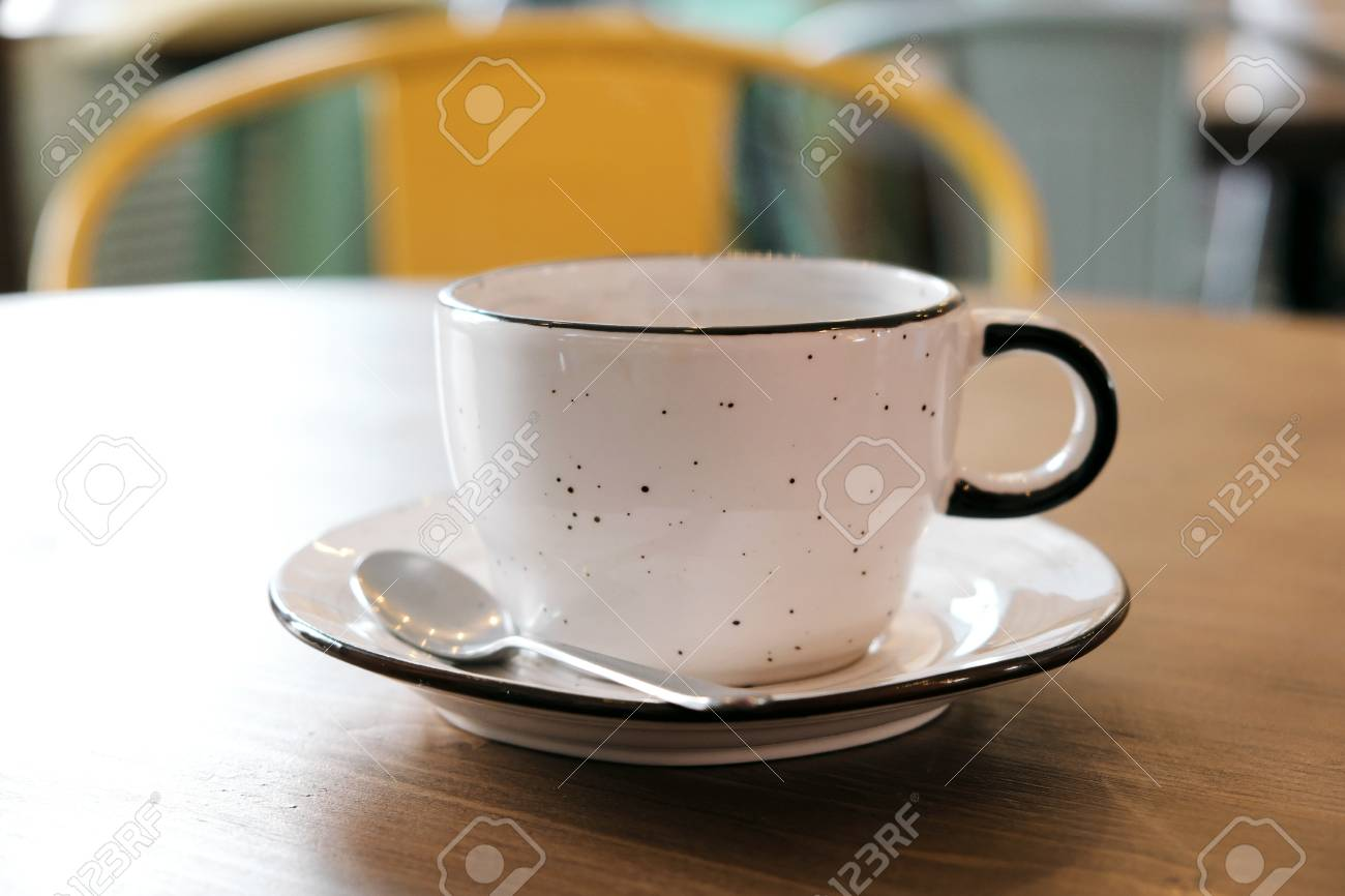 A White Clay Cup With Coffee Stands On A Wooden Table Next To It Is