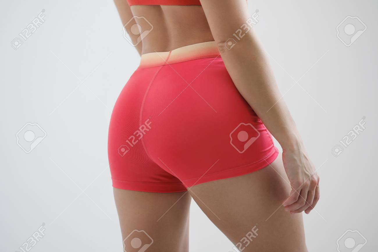 Booty girl in a red sportswear on a light background close-up. - 121512369