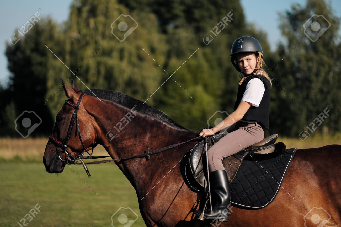 Girl teenager jockey sits on a brown horse in nature. Dressage horses, rider training. - 128929373