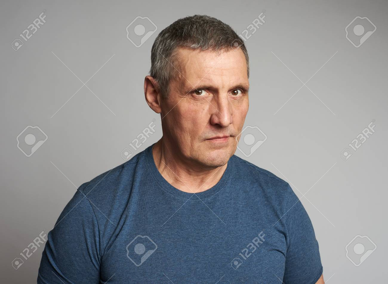 Senior man in blue t-shirt isolated on grey background - 121854999
