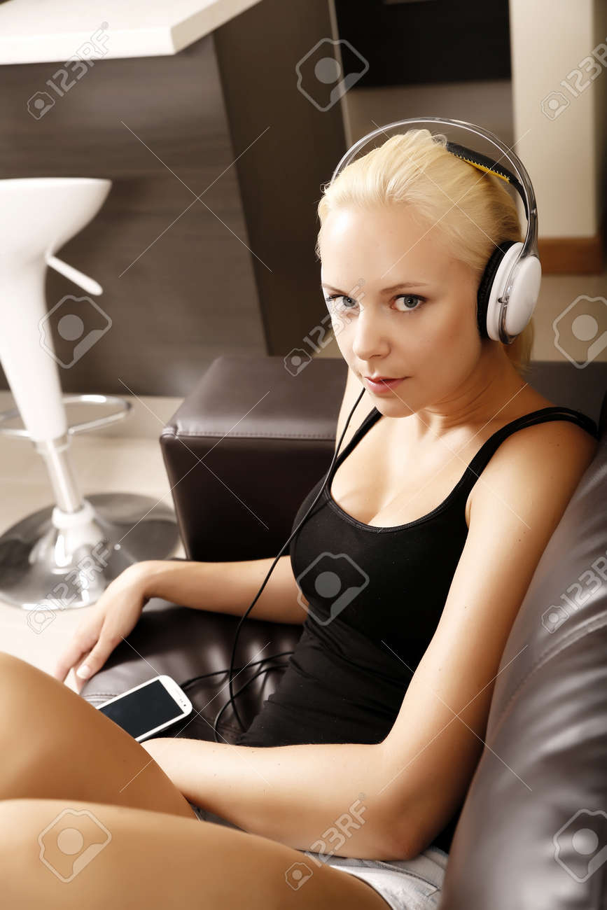 A blonde girl with Headphones sitting on the sofa. Stock Photo - 21159553