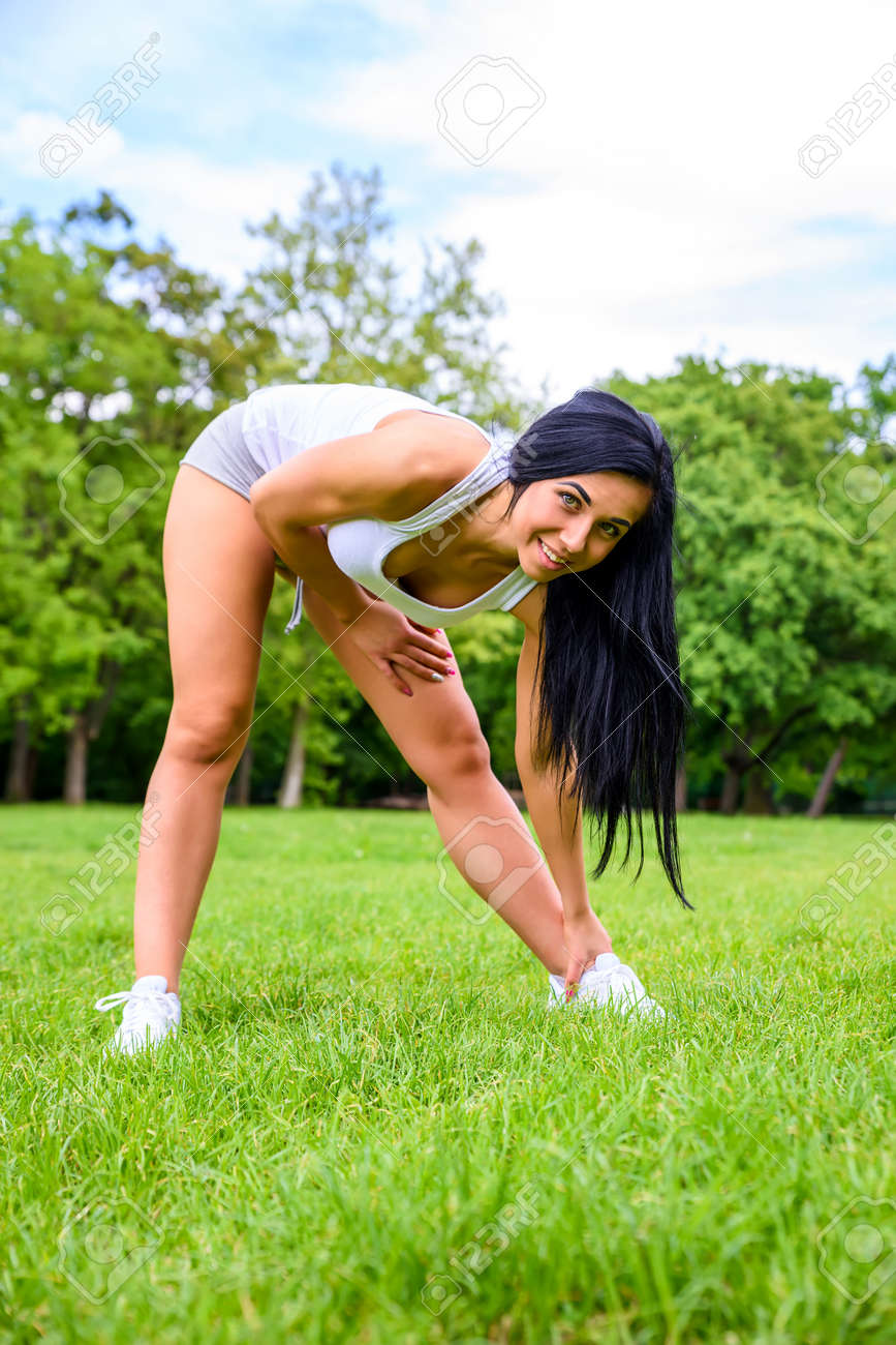 Beautiful young sporty girl in a park - 120069998