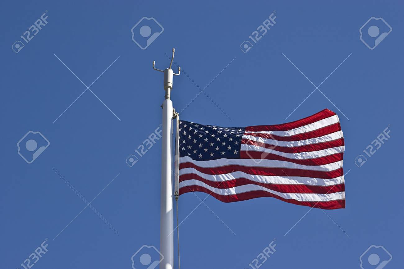 American flag waving in the wind against a blue sky Stock Photo - 4026190